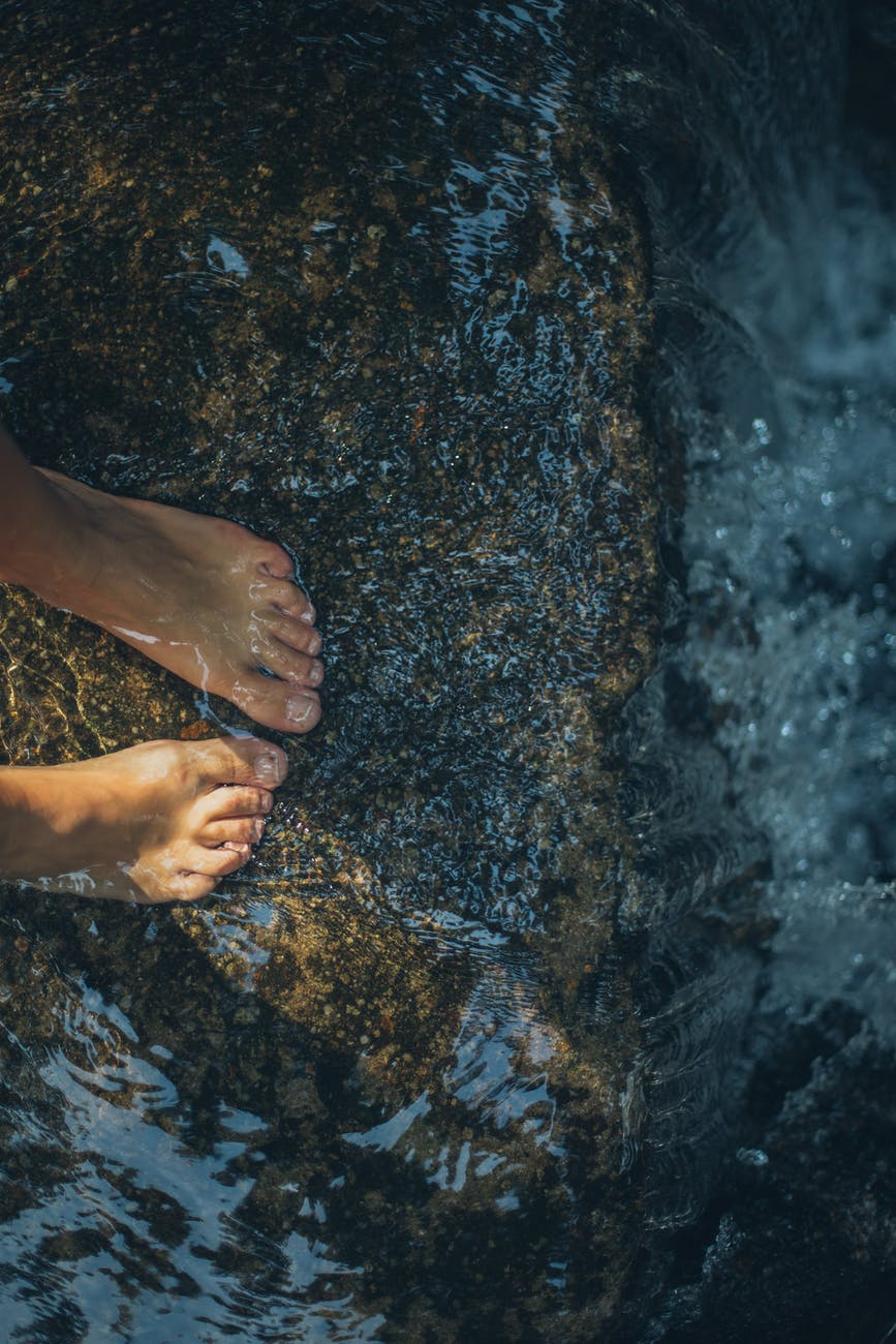 person s feet in water